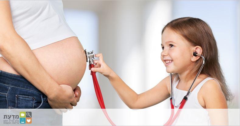 ילדה מקשיבה עם סטטוסקופ לבטן של אישה בהריון