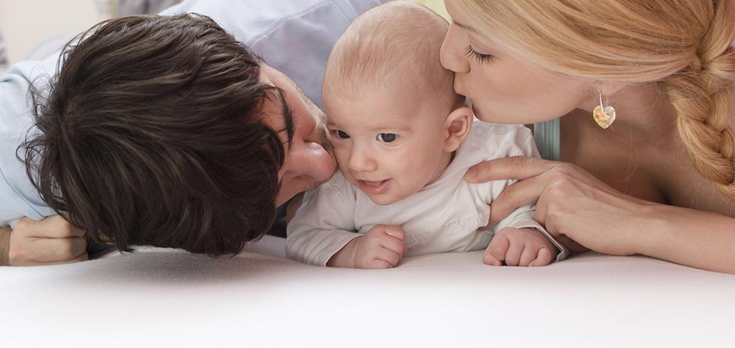 הבאת ילדים לעולם - אפשר גם עם HIV. תמונה של הורים מנשקים תינוק