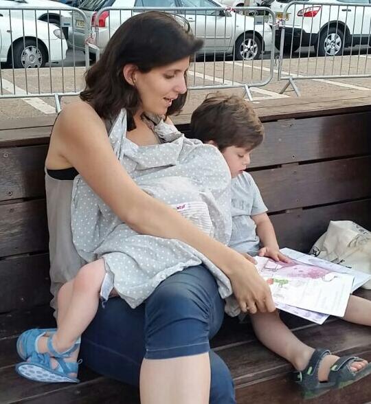 נטע עם שני ילדיה: מניקה את הבת ומסתכלת בחוברת עם הבן