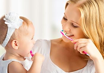 אמא ובת מצחצחות שיניים ביחד